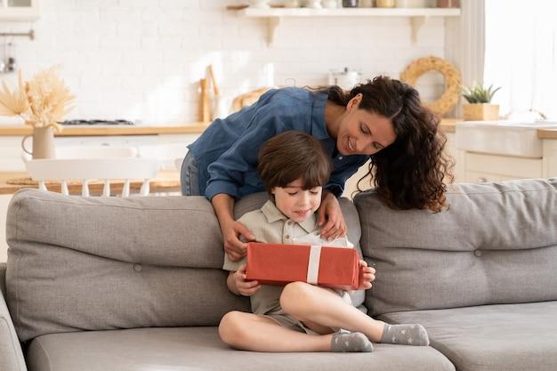 Verjaardag van kind in familiale zorgzame moeder geeft cadeau in huidige doos aan opgewonden zoon op jubileum