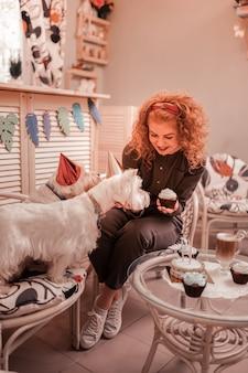Verjaardag vieren. roodharige krullende vrouw met een goed humeur tijdens het vieren van de verjaardag van haar honden