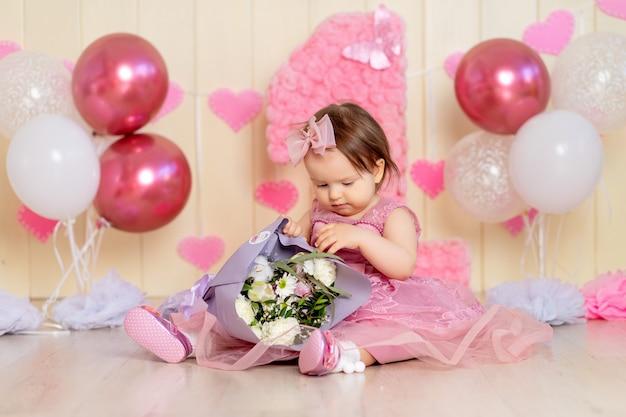 Verjaardagsbaby één jaar oud in roze bloemen met grote en ballen, baby met bloemen