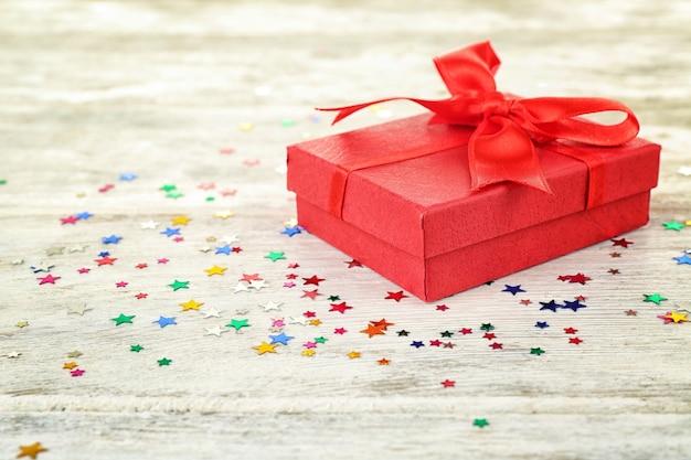 Verjaardagscadeau en kleurrijke confetti op houten oppervlak