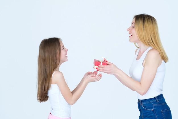Verjaardagscadeau in een rode doos. moeder feliciteert haar dochter met een cadeautje.