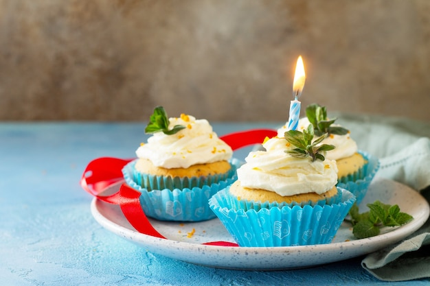 Verjaardagscupcake met slagroompapaver en sinaasappelschil kopieer de ruimte