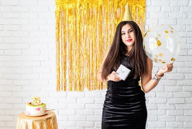 Verjaardagsfeest. beautiful jonge vrouw in feestjurk en verjaardagshoed met ballon op gouden achtergrond