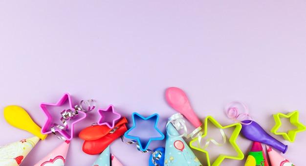 Verjaardagsfeest caps, ballon en sterren op paarse achtergrond.