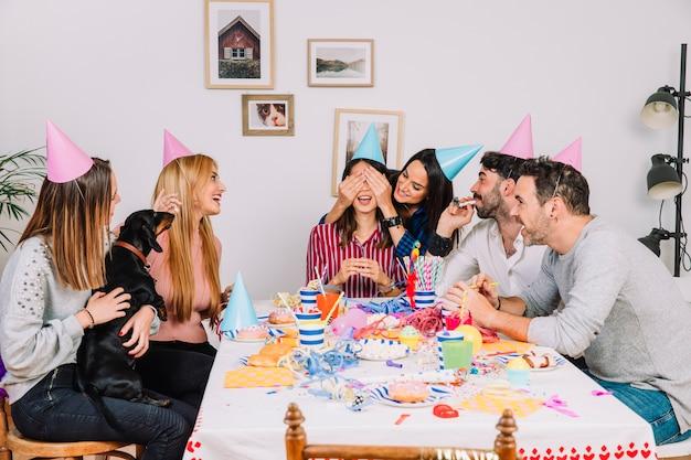 Verjaardagsfeest concept met zes vrienden en een hond