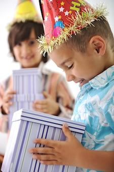 Verjaardagsfeest, gelukkige kinderen vieren, ballonnen en presenteert rond