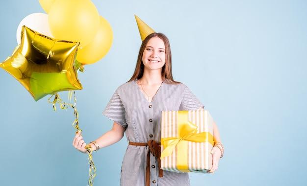 Verjaardagsfeest. jonge vrouw in een verjaardagshoed met ballonnen en grote geschenkdoos verjaardagsfeestje vieren over blauwe achtergrond met kopie ruimte