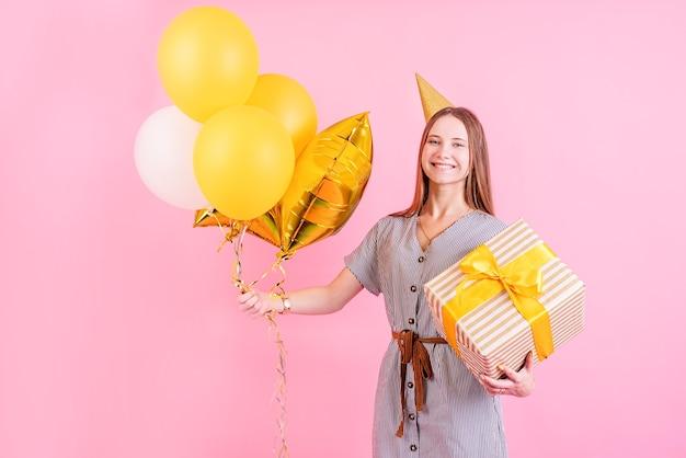 Verjaardagsfeest. jonge vrouw in een verjaardagshoed met ballonnen en grote geschenkdoos verjaardagsfeestje vieren over roze achtergrond met kopie ruimte