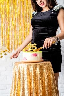 Verjaardagsfeest. mooie brunette vrouw in zwarte feestjurk bedrijf ballon viert haar verjaardag snijden de taart