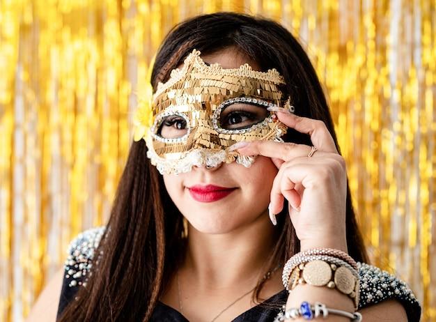 Verjaardagsfeest. mooie brunette vrouw in zwarte feestjurk glanzend gouden maskerademasker dragen
