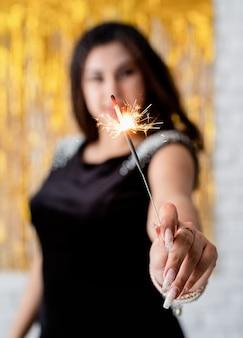 Verjaardagsfeest. mooie jonge vrouw met sterretje en ballon op gouden achtergrond