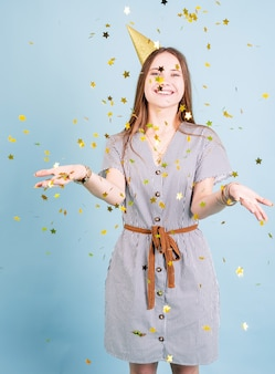 Verjaardagsfeest. tennager meisje met gouden verjaardag hoed confetti blazen over blauwe achtergrond