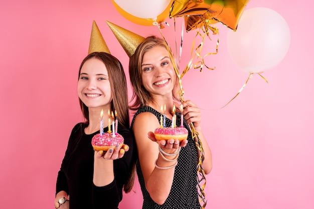 Verjaardagsfeest. twee glimlachende jonge vrouwen of zusters die in verjaardagshoeden verjaardag vieren die donuts met kaarsen over roze achtergrond houden