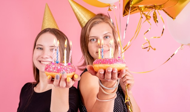 Verjaardagsfeest. twee vriendinnen vieren verjaardag dragen gouden verjaardag hoeden houden van ballonnen en roze donuts met kaarsen op roze achtergrond