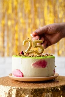 Verjaardagsfeest. vrouw hand viert haar verjaardag verlichting de kaarsen 25 op de taart