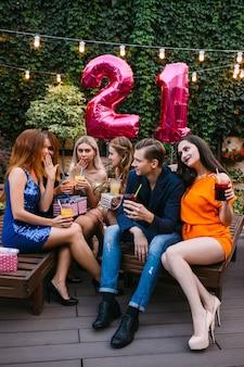 Verjaardagsfeestje buiten. jongeren bedrijf. flirterige stemming, verlegen vrouwtjes. vrouwenaandacht voor jonge man, romantische relaties, viering en roddelconcept.