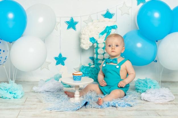 Verjaardagsfeestje een jaar oude jongen in blauw met ballonnen en cake, vakantie en decor concept, baby met cake