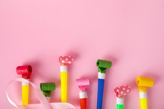 Verjaardagsfeestje fluitjes op roze achtergrond, kleurrijke viering met partijblazer hoorns, minimaal partijconcept.