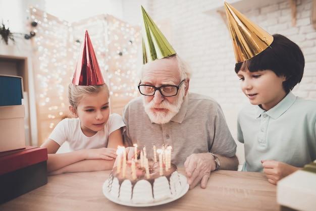 Verjaardagsfeestje grootvader blaast kaarsjes uit.