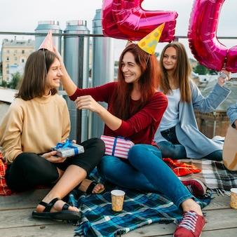 Verjaardagsfeestje leuk. vrolijke meisjes dragen grappige hoeden en geven cadeautjes. buiten feest. vriendschap concept