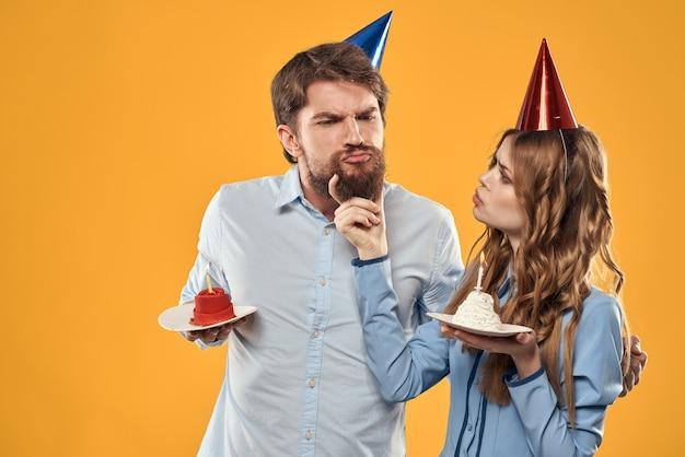Verjaardagsfeestje man en vrouw in een pet met een taart op een gele achtergrond bijgesneden weergave. hoge kwaliteit foto