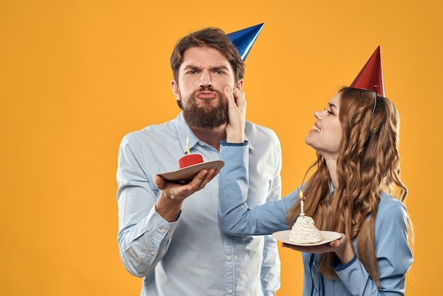 Verjaardagsfeestje man en vrouw in een pet met een taart op een gele bijgesneden weergave