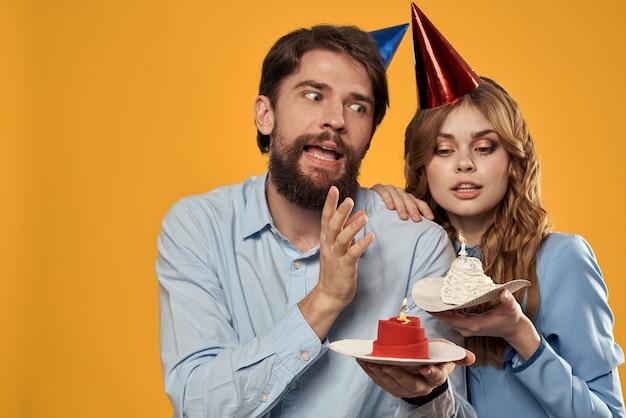 Verjaardagsfeestje man en vrouw op een geel in hoeden met een taart in hun handen