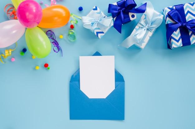 Verjaardagsfeestje met ballonnen, geschenkdozen, envelop met briefje en confetti