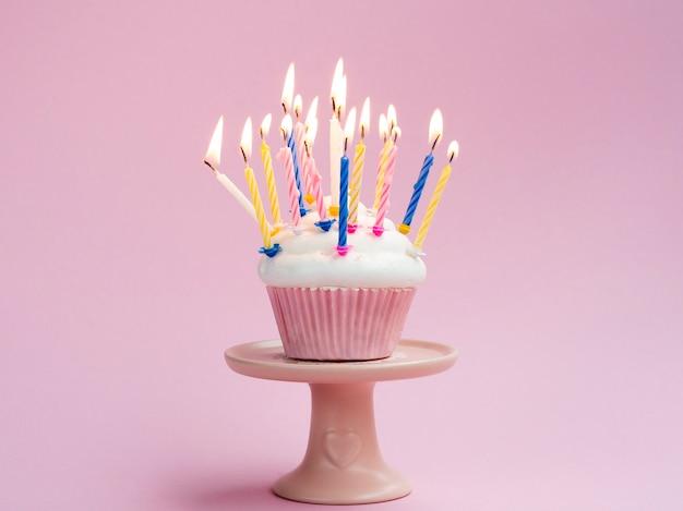 Verjaardagsmuffin met kleurrijke kaarsen op roze achtergrond