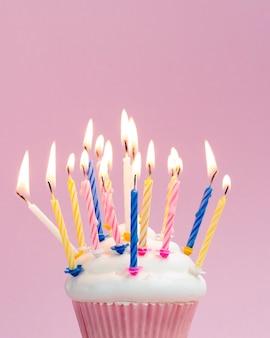 Verjaardagsmuffin met kleurrijke kaarsen