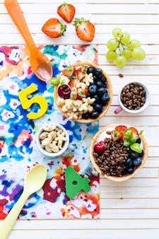 Verjaardagsontbijtkommen voor kinderen met ontbijtgranen en bessen
