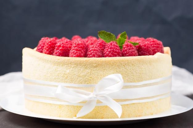 Verjaardagsspongecake met frambozen verfraaide witte lint en boog