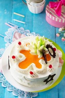Verjaardagstaart biscuit met slagroom met kleurrijke kaarsen op een blauwe achtergrond kopieer de ruimte