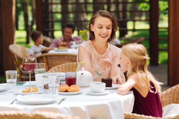 Verjaardagstaart. blond meisje voelt zich buitengewoon gelukkig tijdens het eten van haar verjaardagstaart zittend in de buurt van moeder
