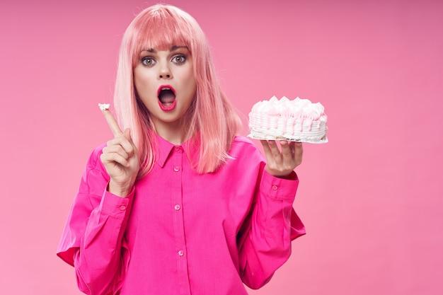 Verjaardagstaart en mooie vrouw in roze pruik