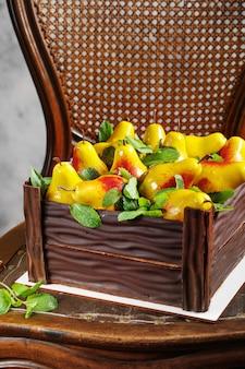 Verjaardagstaart in de vorm van een chocoladedoos gevuld met peren gemaakt van moussecake