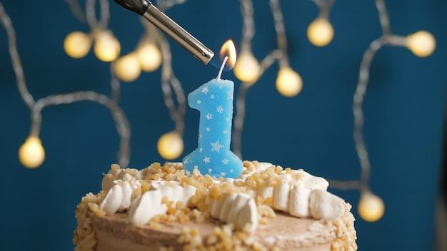 Verjaardagstaart met 1 cijfer kaars op blauwe backgraund in brand gestoken door aansteker. detailopname