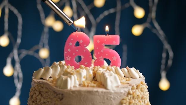 Verjaardagstaart met 65 nummer roze kaars op blauwe achtergrond in brand gestoken door aansteker. close-upweergave
