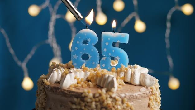 Verjaardagstaart met 65 nummerkaars op blauwe achtergrond in brand gestoken door aansteker. detailopname