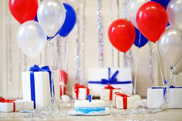 Verjaardagstaart met een kaars 1 jaar en dozen met geschenken.