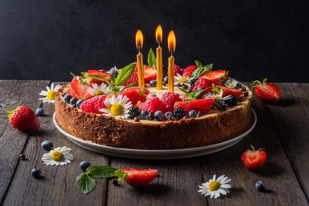 Verjaardagstaart met kaarsjes cheesecake pie met verse bessen aardbeien bosbessen braambes