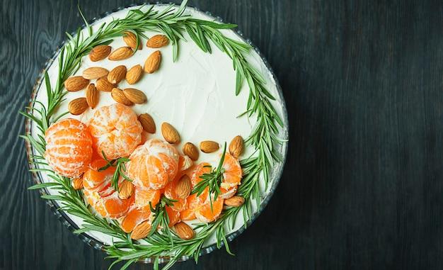 Verjaardagstaart met mandarijnen, amandelen en rozemarijn op een standaard. kersttaart op een donkere achtergrond. uitzicht van boven. ruimte kopiëren.