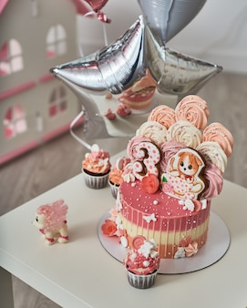 Verjaardagstaart voor 3 jaar versierd met vlinders peperkoek kitten met slagroom en het nummer drie. meringue lichtroze in de vorm van een roos of bloem. meringue is veel taartdecoratie