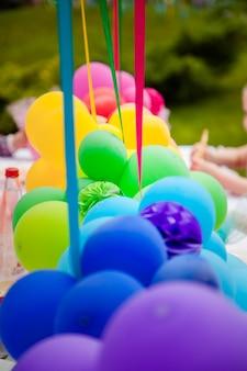 Verjaardagstafel met regenboogballonnen. zomervakantie in het park.