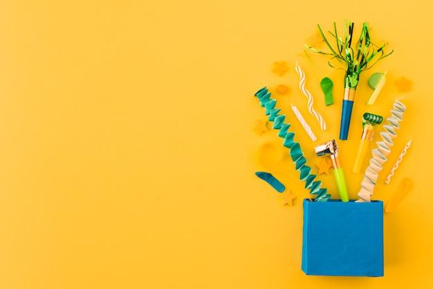 Verjaardagstoebehoren gemorst uit van papieren zak op oranje achtergrond