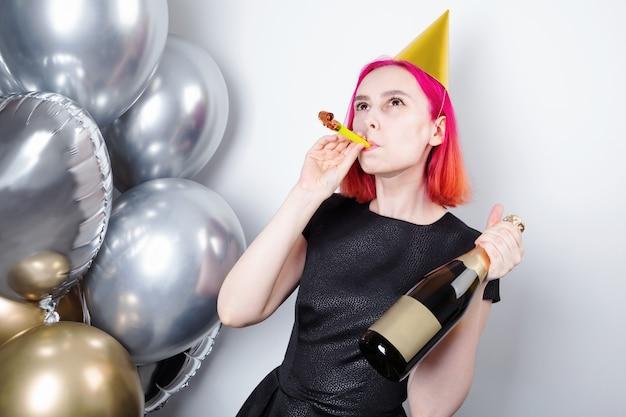 Verjaardagsviering. jonge gelukkige vrouw met roze haar met vakantiepet en pijp houdt fles champagne in de hand, zilveren en gouden ballen