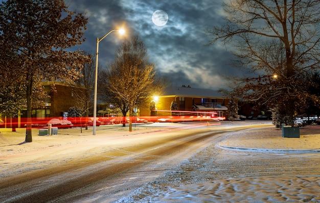 Verkeer bij nacht in de behandelde sneeuw, de mooie stad van de nachtweg