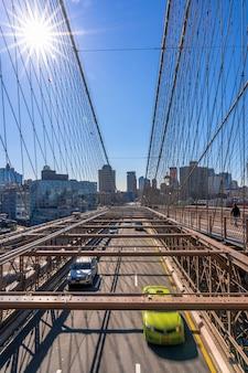 Verkeer in ochtendspitsuur vóór werkdag op de brug van brooklyn over cityscape van new york muur, de vs, verenigde staten, bedrijfs en vervoersconcept