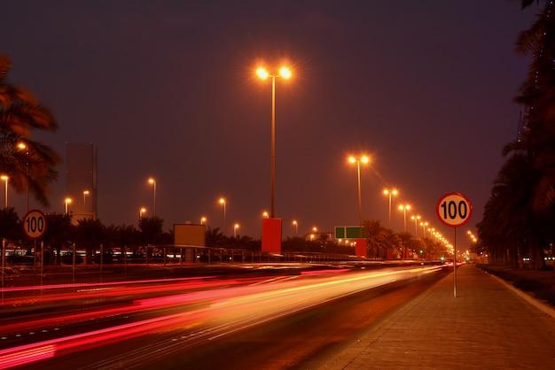 Verkeer 's nachts in de stad met lichte paden van de kleurenauto
