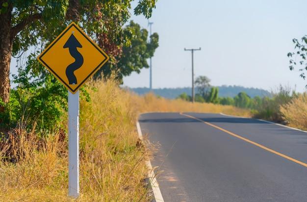 Verkeer waarschuwt afdaling. verlaag de snelheid en gebruik een lagere versnelling. pijl verkeersbord met blauwe hemel. waarschuwingsbord op straat.